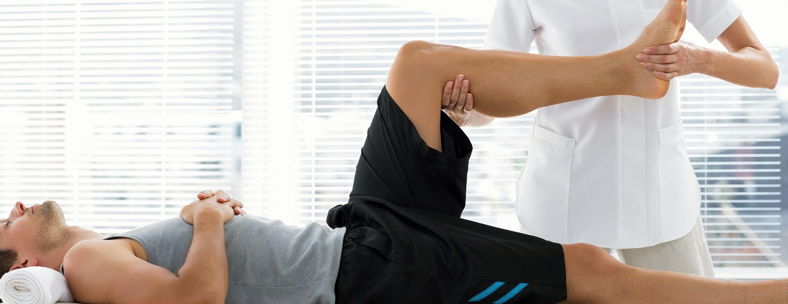 Physiotherapist assessing patients leg